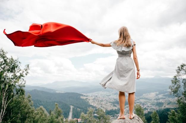 La mujer en montañas salvajes da señal de socorro sos usando la cubierta roja.