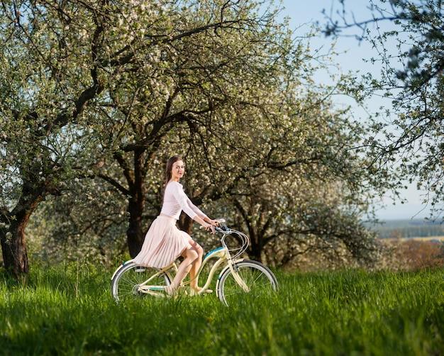 Mujer montando una bicicleta blanca retro en el jardín de primavera en el día soleado