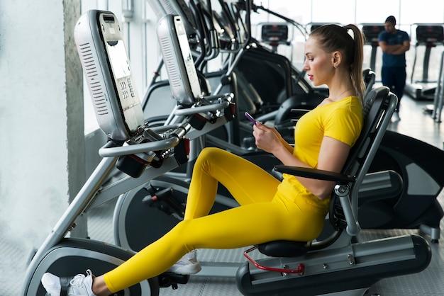 Mujer montando bicicleta estática horizontal en el gimnasio
