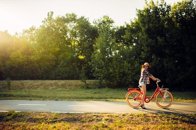 Mujer montando en bicicleta vintage en el parque de verano