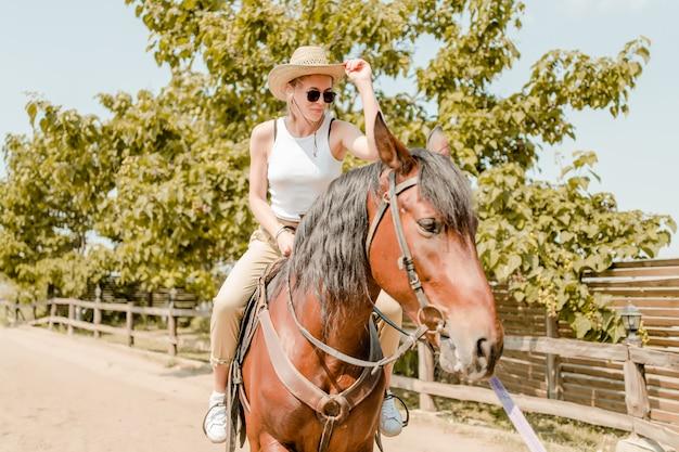 Mujer montando a caballo en una granja