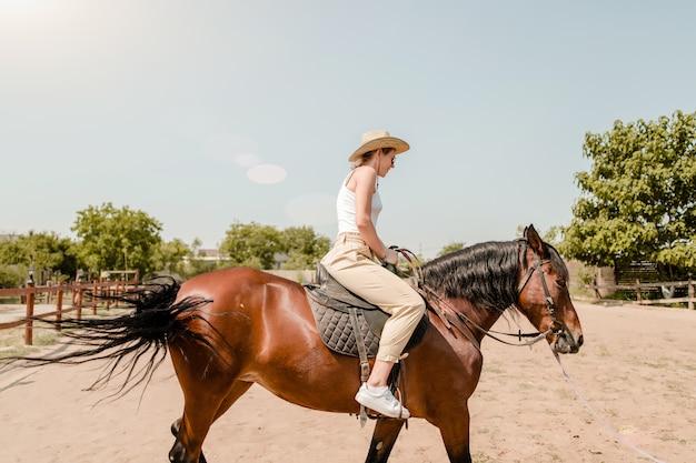 Mujer montando a caballo en un pueblo