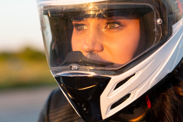 Mujer montando su motocicleta con casco