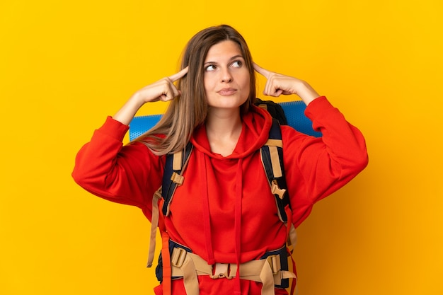 Mujer montañista eslovaca con una gran mochila aislada sobre fondo amarillo que tiene dudas y pensamiento