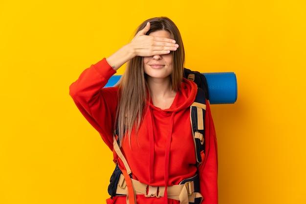 Mujer montañista eslovaca con una mochila grande aislada sobre fondo amarillo que cubre los ojos con las manos. no quiero ver algo
