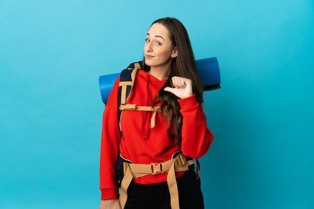 Mujer montañista con una gran mochila sobre antecedentes aislados orgullosa y autosuficiente