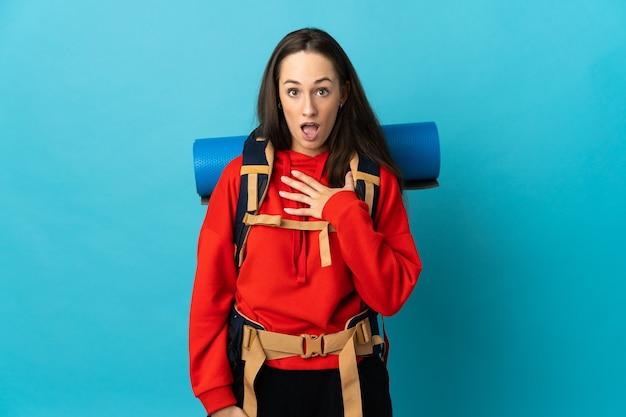 Mujer montañista con una mochila grande sobre fondo aislado sorprendido y conmocionado mientras mira a la derecha