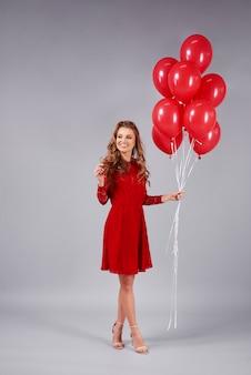 Mujer con un montón de globos mirando espacio de copia