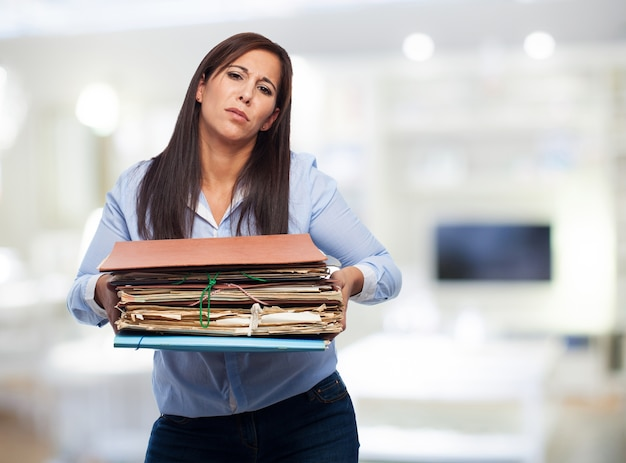 Mujer con un montón de papeles y carpetas