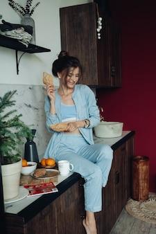 Mujer morena alegre sosteniendo pasteles en la cocina