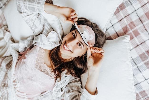 Mujer morena, con, antifaz para dormir, mentira en cama