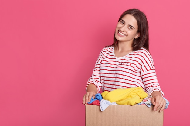 Mujer morena con apariencia agradable, de pie con la caja en las manos contra la pared rosa