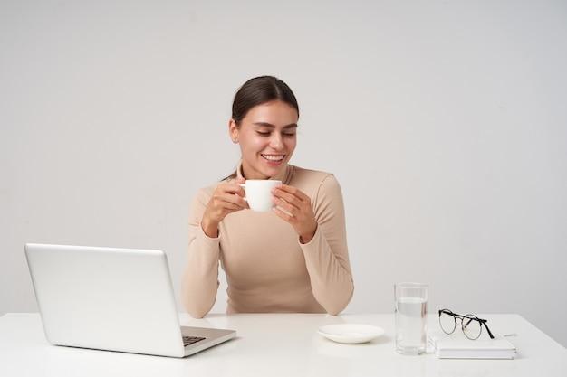 Mujer morena atractiva joven positiva con peinado elegante manteniendo cerámica blanca en sus manos y sonriendo alegremente, sentado en la mesa sobre la pared blanca