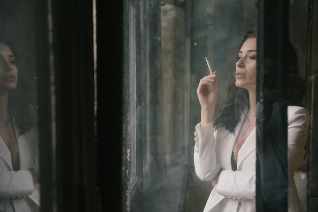 Mujer morena atractiva joven en el traje que fuma un cigarrillo por la ventana dentro