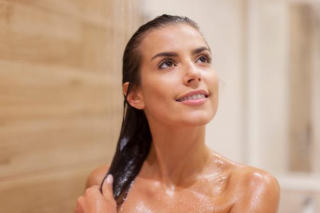 Mujer morena atractiva tomando ducha