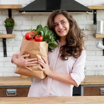 Mujer morena con bolsa de papel con alimentos sanos