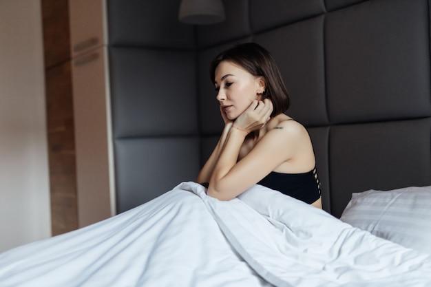 Mujer morena de cabello bastante largo en cama blanca en la suave luz de la mañana debajo del edredón