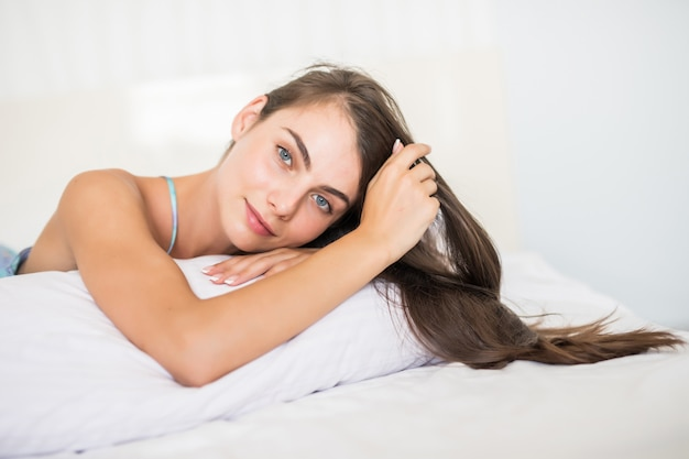 Mujer morena casual sonriente que miente en su cama en dormitorio brillante