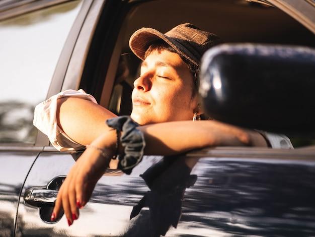 Mujer morena en un coche negro bajo la luz del sol