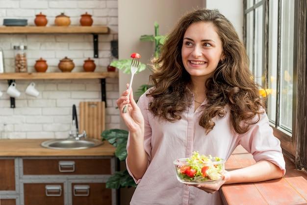 Mujer morena comiendo una ensalada
