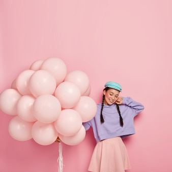 Mujer morena complacida con dos trenzas, viste una elegante gorra, sudadera suelta morada y falda rosada, sostiene globos de helio