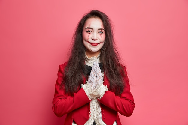 Mujer morena complacida con maquillaje ensangrentado mantiene las palmas presionadas juntas pide hacer favor viste traje rojo y guantes de encaje posa contra la pared rosa