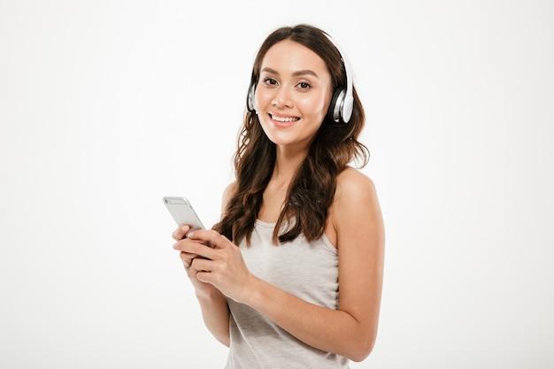 Mujer morena contenta en auriculares escuchando música y sosteniendo el teléfono inteligente mientras mira a la cámara sobre gris