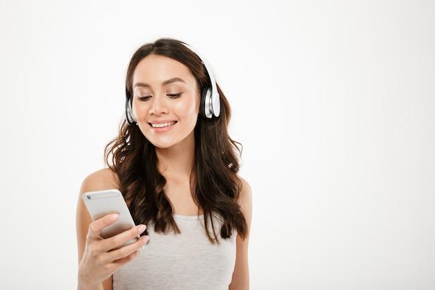 Mujer morena contenta en auriculares escuchando música y usando el teléfono inteligente sobre gris