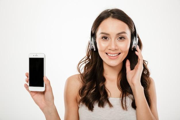 Mujer morena contenta en auriculares mostrando la pantalla del teléfono inteligente en blanco y mirando a la cámara sobre gris