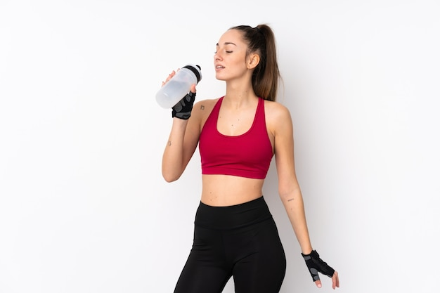 Mujer morena deporte joven sobre pared blanca aislada con botella de agua deportiva