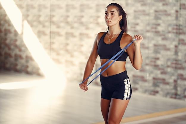 Mujer morena deportiva en un entrenamiento de ropa deportiva en un gimnasio