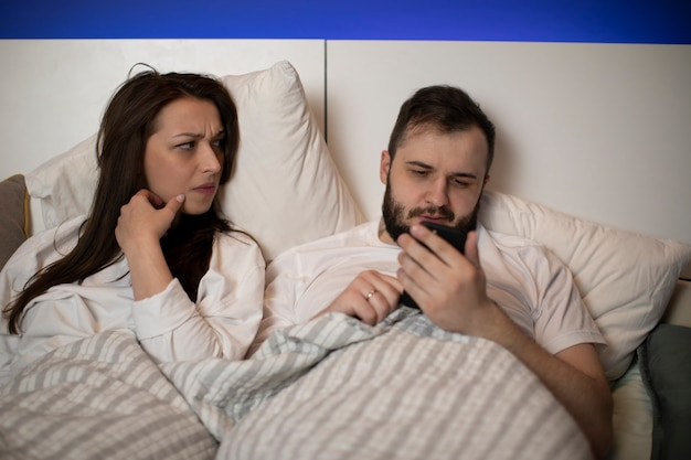 Mujer morena descontenta celosamente mira a su novio barbudo charlando con alguien en su teléfono inteligente