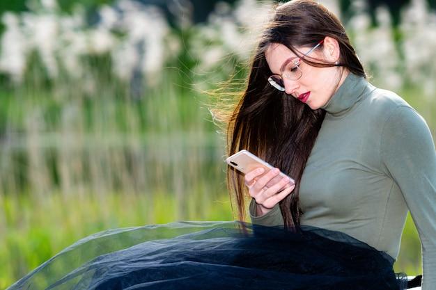 La mujer morena emocional hermosa joven se siente triste cuando lee el mensaje en el teléfono inteligente