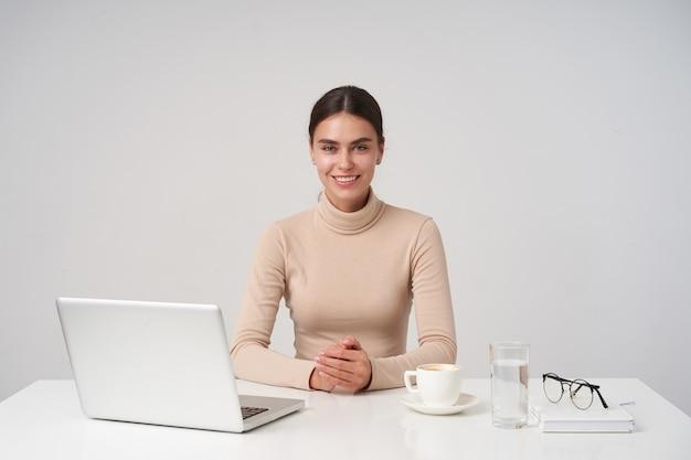 Mujer morena encantadora joven alegre con peinado de cola de caballo mirando positivamente y sonriendo ampliamente mientras posa sobre una pared blanca con una computadora portátil y una taza de café
