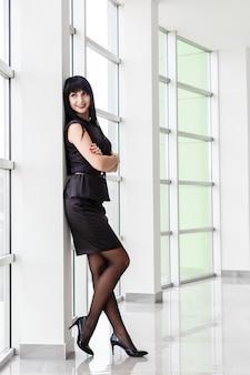 La mujer morena feliz atractiva joven vestida en un traje de negocios negro con una falda corta se está colocando cerca de la ventana en una oficina blanca, sonriendo.