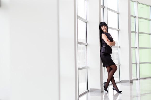 La mujer morena feliz atractiva joven vestida en un traje de negocios negro con una falda corta se está colocando cerca de la ventana en la oficina, sonriendo, mirando a la cámara.