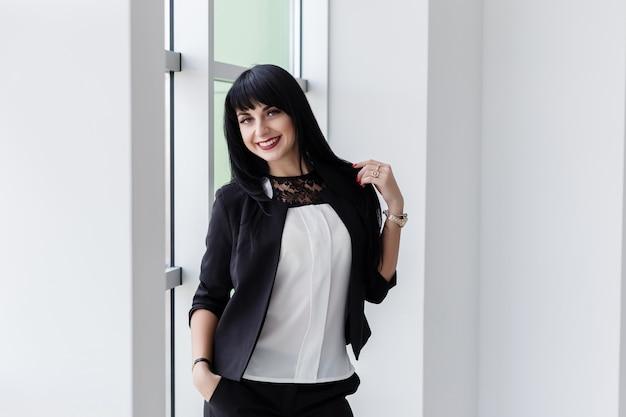 La mujer morena feliz atractiva joven se vistió en un traje de negocios negro que se colocaba cerca de la ventana en oficina, sonriendo, mirando la cámara.