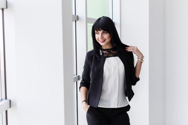 La mujer morena feliz atractiva joven se vistió en un traje de negocios negro que se colocaba cerca de la ventana en una oficina, sonriendo, mirando a la ventana.