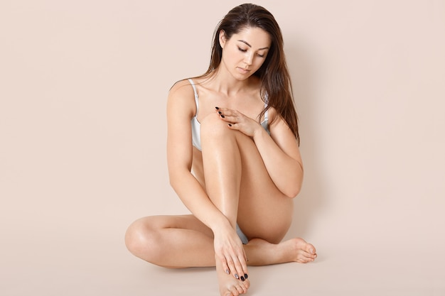 La mujer morena con una figura perfecta, posa en sujetador, muestra una piel suave y perfecta, tiene el pelo largo y oscuro, las modelos sobre la pared beige llevan un estilo de vida saludable. personas, feminidad y bienestar.