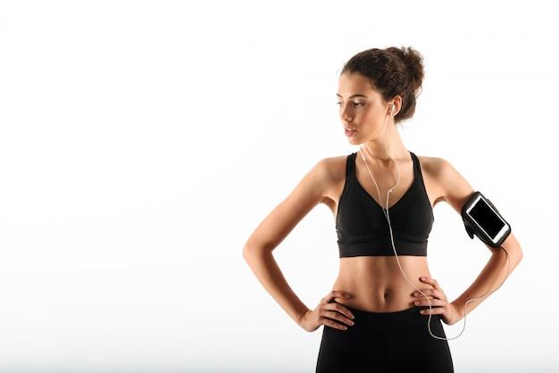 Mujer morena fitness bastante rizada sosteniendo los brazos en las caderas y escuchando música mientras mira lejos
