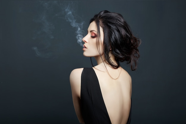 Mujer morena fumando sobre fondo oscuro