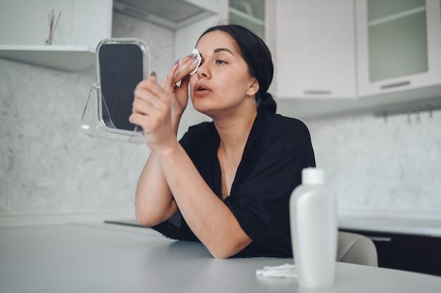 Mujer morena hermosa que quita maquillaje de su cara con el espejo. linda hermosa belleza natural chica limpieza cara con esponja de algodón. cosmetología y spa, cuidado de la piel con problemas, concepto de tratamiento del acné