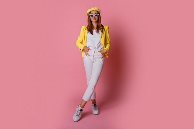 Mujer morena inspirada en chaqueta amarilla y boina saltando sobre rosa