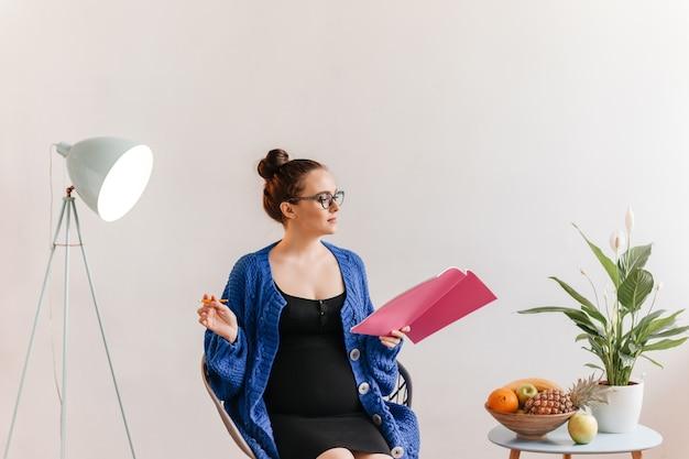 Mujer morena inteligente en chaqueta de punto azul oscuro lee el libro. señora embarazada en vestido negro sostiene la pluma y toma notas.