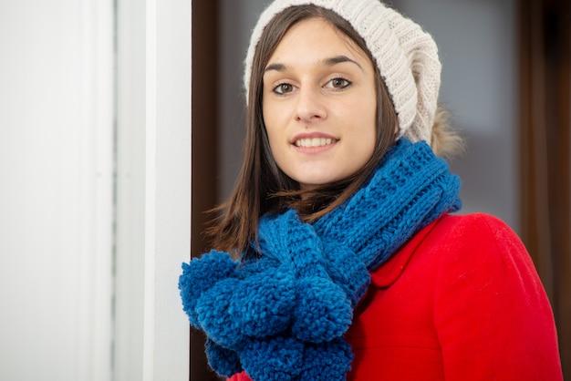 Mujer morena joven con abrigo y gorra de invierno