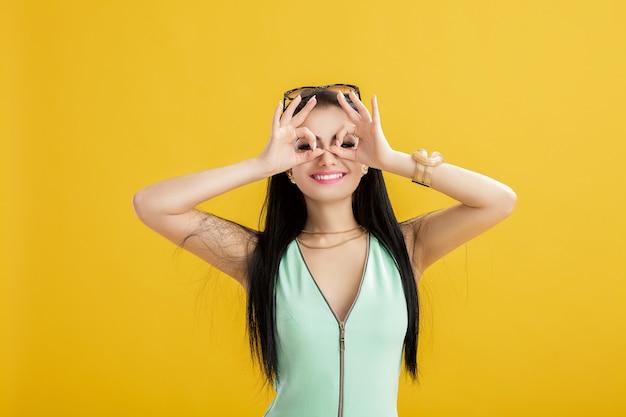 Mujer morena joven atractiva en un traje de baño verde sobre un amarillo. mujer divertida en un traje turquesa