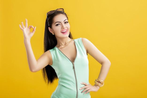 Mujer morena joven atractiva en un traje de baño verde sobre un amarillo. mujer sexy de verano en un traje turquesa que muestra el signo de ok