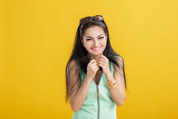 Mujer morena joven atractiva en un traje de baño verde sobre un amarillo. mujer sonriente en un traje turquesa