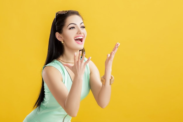 Mujer morena joven atractiva en un traje de baño verde sobre un amarillo. mujer sorprendida en un traje turquesa