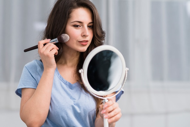Mujer morena joven con el cepillo del maquillaje que mira en espejo